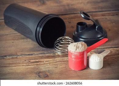 Whey protein powder in scoop  and plastic shaker on wooden background. Selective focus, shallow DOF