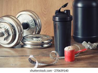 Whey protein powder in scoop with  plastic shaker on wooden background