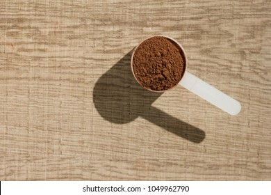 Whey protein powder sports bodybuilding supplement. Minimalism and hard light. Measuring scoop full with chocolate flavour powder on wooden background.