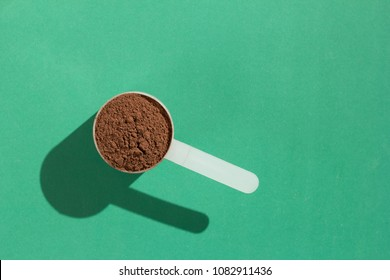 Whey protein powder sports bodybuilding supplement. Minimal concept and hard light. Scoop with chocolate flavoured powder on green background.