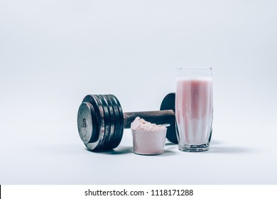 Whey protein shake in a glass next to scoop of powder and dumbbell on a white background. Fitness nutrition drink and heavy weights.