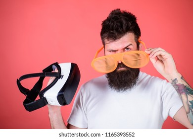 Which glasses choose louvered or virtual. Man making decision what choose real or virtual. Man bearded hipster with virtual reality headset and louvered sunglasses red background. Alternative reality.