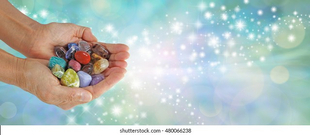 Which Stone attracts you - Female  cupped hands full of tumbled multicolored healing crystals on a pale jade green bokeh background with streams of glittering sparkles and copy space