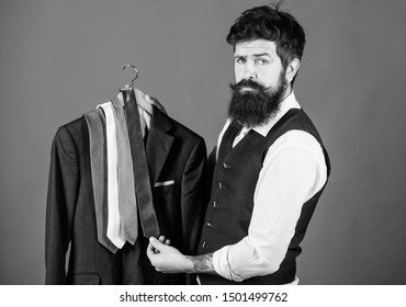 Which tie should I wear. Bearded man matching neck tie color to coat. Brutal hipster holding colorful tie collection and suit jacket. Choosing a perfect tie.