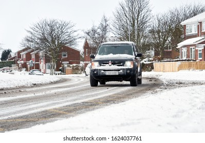 WHICKHAM, NEWCASTLE UPON TYNE, ENGLAND, UK - FEBRUARY 28, 2018: A 4x4 Landrover driving along a snow and ice covered road in a housing estate.