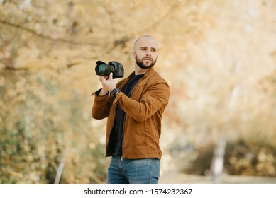 While bald stylish photographer with a beard in a suede leather jacket, blue shirt and jeans with digital wristwatch looks through photos in his camera, he drew attention to something in the forest in
