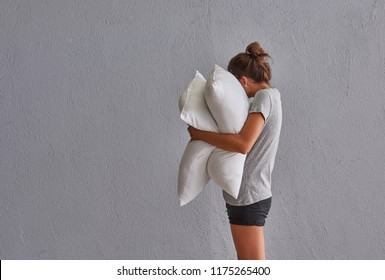 while girl hug a pillow in front of the grey wall. Girl is sleeping.