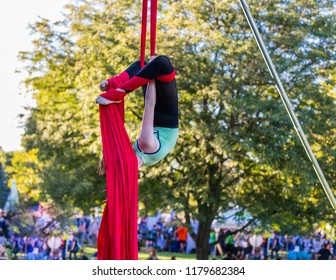 While hanging upside down, a young lady is hiding her head with a red ribbon