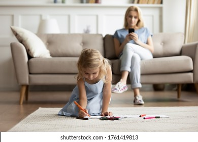 While little daughter drawing with colorful felt-tip pens on album sit on carpet warm floor mom rest on sofa with smartphone gadget device ignoring kid. Weekend leisure, free time, modern home concept
