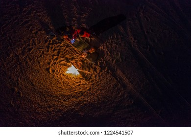 While looking for meteorites at Atacama Desert we made a stop for sleeping in the middle of the amazing Atacama Desert. Two people on a camp fire under the full moon light on a starry night. Chile