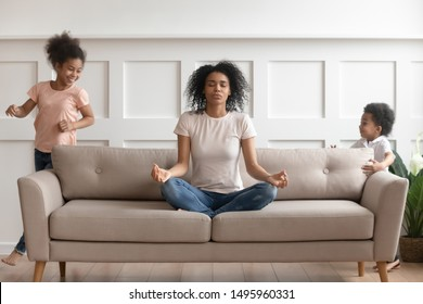 While noisy daughter and son kids run playing tag-game in living room near young african mother she meditates sit in lotus pose on couch reached zen feel tranquil, stress relief self-control concept
