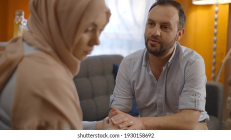 While the sad Muslim woman wearing a headscarf is looking sad with her eyes and she continues to feel sad despite her husband is giving comfort of her. Concept of consoling husband and wife.