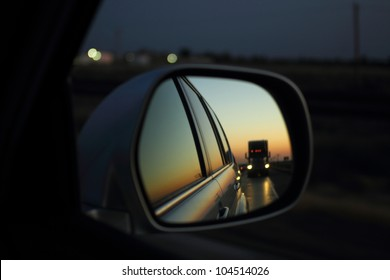 While traveling on a highway the reflection of a semi-trailer truck on the right side mirror of an SUV during sunset.