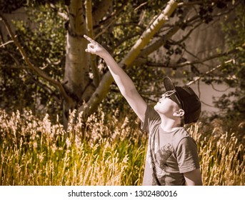 While watching the solar eclipse of 2017 from Palisades Lake in Idaho, a boy wearing cheap paper glasses points up at the sky in amazement.