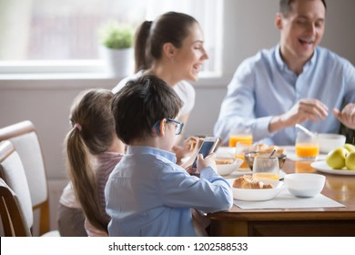 While whole family eating talking having breakfast, little preschool son in glasses holding using smartphone looking at screen. Bad habit overuse of devices and gadgets, mobile phone addiction concept