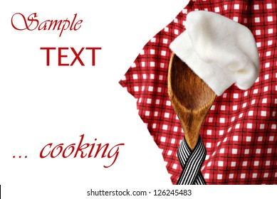Whimsical cooking concept of vintage wooden spoon 'wearing' a chef's hat with red checkered napkin in soft focus as background.  Macro on white background with copy space.