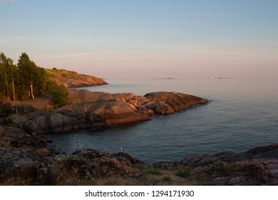 The whimsical rocky shoreline of Suomenlinna, the bay and the view of the Gulf of Finland on a quiet summer evening in Finland. Beautiful nature of Finland.