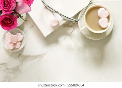 Whimsical, romantic desk top with studious objects, roses and hot chocolate with heart shaped marshmallows. Room for copy