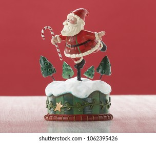 Whimsical Santa music box with stylized trees and candy cane accents on red background.