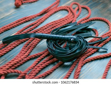 Whip for bondage and rope to tie on a dark background. Accesories for sexual games.