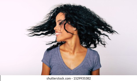 I whip my hair back and forth. Charming Afro-American lady with frizzy dark hair is whipping her hair with her eyes closed while laughing with joy.