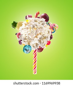 Whipped chantilly cream lolipop concept. Round whipped milk shake cream like lollipop with candy, sweets and candy on border, isolated on bright background. Cream swirl lolly with childs colorful