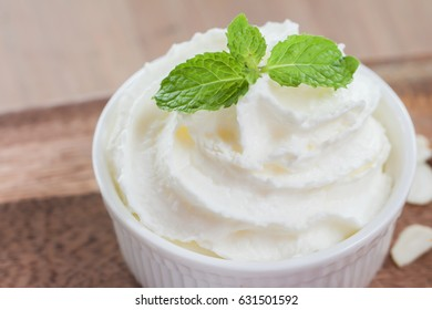 Whipped cream with peppermint leafs in ceramic cup
