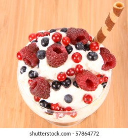 Whipped cream with raspberries, red currants and blue berries in a glass cup, decorated with a wafer tube on wooden background