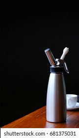 Whipped cream stainless container, can, bottle, whipping cream, white coffee cup on the wooden table with black background, isolated, food and drink
