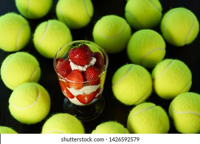 Whipped cream and strawberries served in a glass. Dark wooden table, tennis ball, high resolution