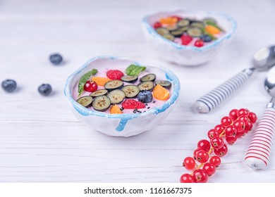 Whipped quark mousse with raspberries, blueberries, red currant and winter cherry on a white wooden background. Free space