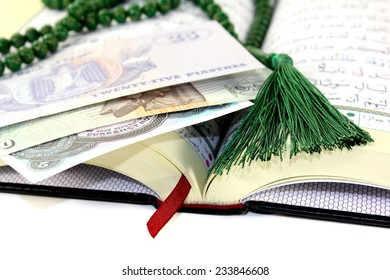 whipped Quran with Egyptian currency before light background