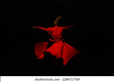 Whirling Dervish with red costume on black background