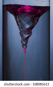 whirlpool with pink mist - vortex in a column of water