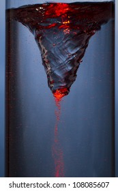 whirlpool with red mist - vortex in a column of water
