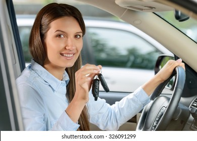In whirlwind of life. Pretty smiling vivacious beautiful young woman holding keys and keeping wheel while  driving a car.