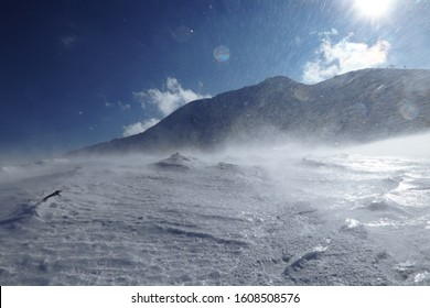 Whirlwind on snowy hilss in Slovakia Low Tatras. Epic wind storm in january with clear sky. Frozen land and snow attack on skier from side. Unpleasant side wind