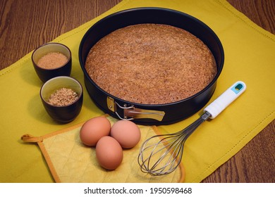 Whisk and baking pan with homemade traditional hazelnut cake from Piedmont (Italy) and raw ingredients: cane sugar, eggs and flour of nocciola piemonte (the typical hazelnut variety of Piedmont)