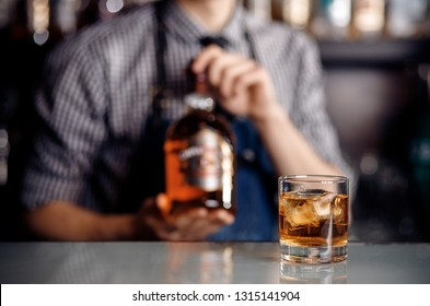 Whiskey alcohol glass with ice on bar, in background barman holds bottle. Dark shade.