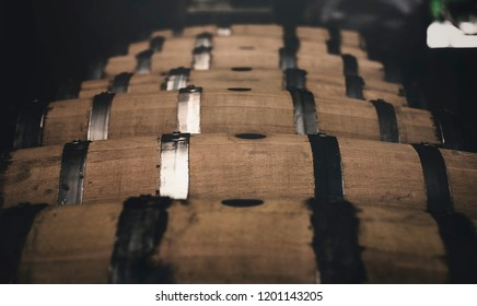 Whiskey barrels racked in a distillery, while aging the fine spirit.