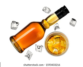 Whiskey bottle with a full glass and  ice cubes, top view