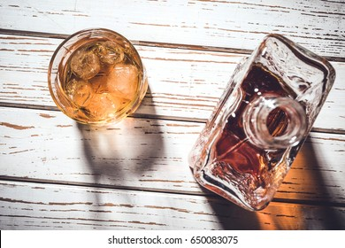 Whiskey bottle and whiskey glass with ice cubes on white wooden table