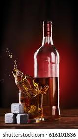 Whiskey bottle with Glass Splashing over Ice stones for whiskey .