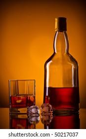 whiskey bottle, ice and glass, orange background