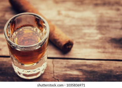 Whiskey or bourbon in a shot glass and cigar