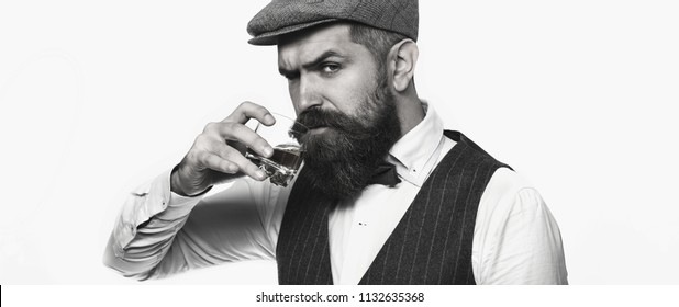Whiskey, brandy, cognac drink. Brutal bearded man with glass of whiskey, brandy, cognac. Attractive man with a cognac. Old hipster style. Black and white.