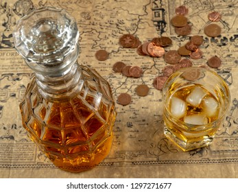 Whiskey or brandy decanter,british coins with a glass of whiskey on a table, covered in old parchment paper map.Soft focus.