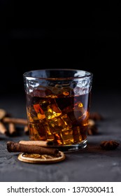 Whiskey, brandy or liquor, with cinnamon, orange, spices and decorations on dark background. Seasonal holidays concept. Close up view, shallow depth of field, image vignetting