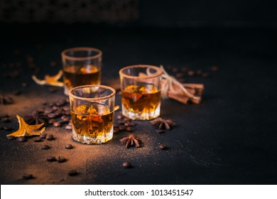 Whiskey, brandy or liquor, coffee beans, spices and decorations on dark background. Seasonal holidays concept.