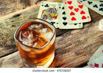 Whiskey, cigar and cards on a wooden background.